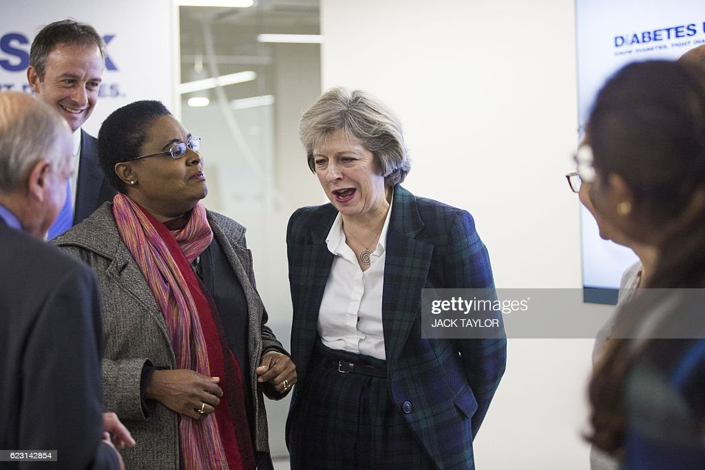Britain's Prime Minister Theresa May (C) speaks with charity Diabetes UK staff and volunteers at the charity's new office in London on November 14, 2016. May, who has been diagnosed with Type 1 diabetes, officially opened the new Diabetes UK office today to coincide with World Diabetes Day. / AFP / POOL / Jack Taylor