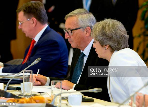 Britain's Prime Minister Theresa May speaks with European Commission President JeanClaude Juncker during a breakfast meeting at on the second day of...