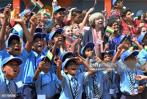 TOPSHOT Britain's Prime Minister Theresa May stands among Indian school children as they watch a flypast by Indian Airforce planes during a visit to...