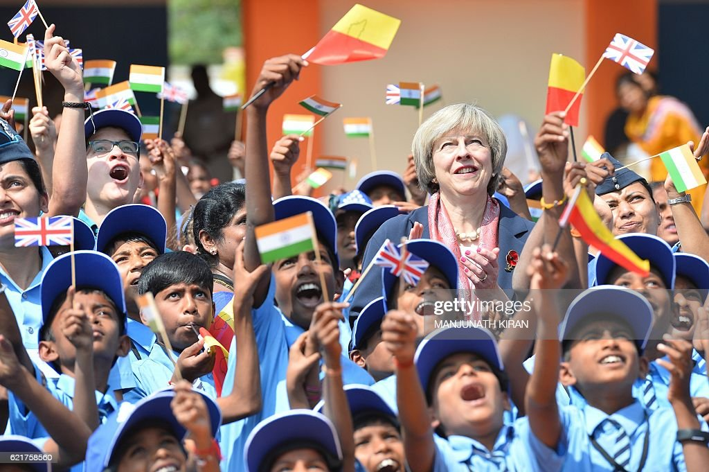 Britain's Prime Minister Theresa May (C) stands among Indian school children as they watch a fly-past by Indian Airforce planes during a visit to a school on the outskirts of Bangalore on November 8, 2016. Britain's Prime Minister Theresa May pledged November 7 to make it easier to do business with India, seeking to boost trade with the world's fastest growing major economy ahead of Brexit, but gave little ground on a key visa demand. / AFP / MANJUNATH