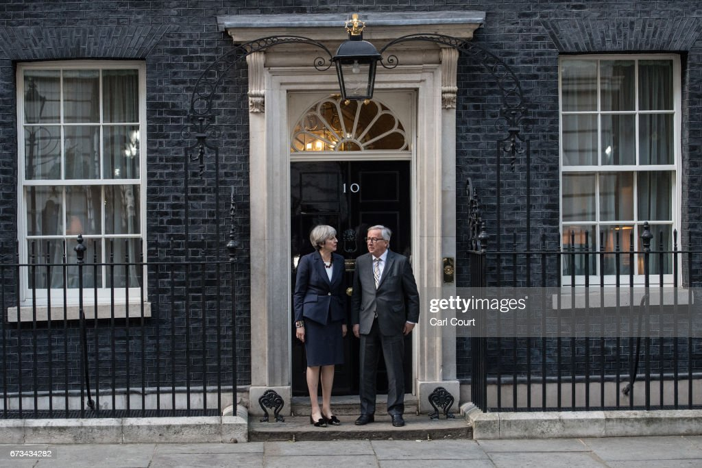 Britain's Prime Minister, Theresa May stands with European Commission president, Jean-Claude Juncker at the front door of 10 Downing Street on April 26, 2017 in London, England. Prime Minister May is to hold her first major talks with E.U leaders since calling a general election in a bid to strengthen her position in forthcoming Brexit negotiations.
