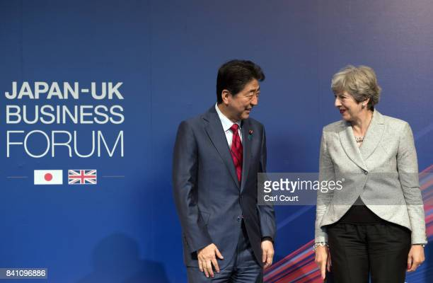 Britain's Prime Minister Theresa May stands with Japan's Prime Minister Shinzo Abe as they attend a JapanUK Business Forum on August 31 2017 in Tokyo...