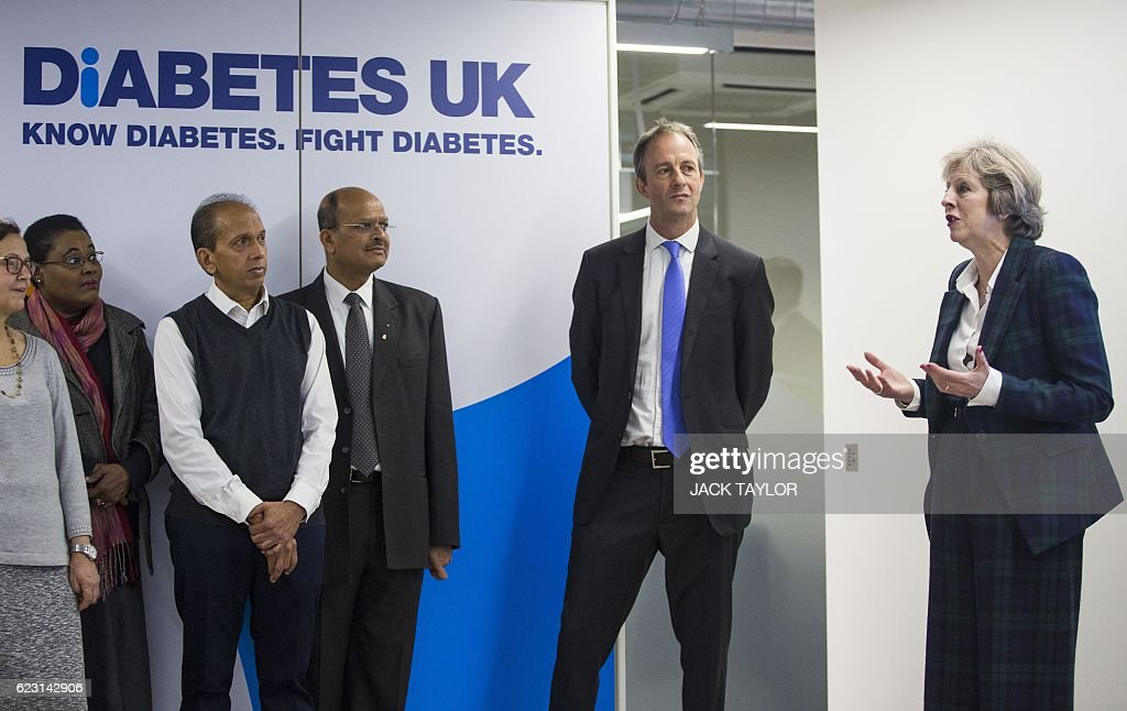 Britain's Prime Minister Theresa May (R) stood with charity Diabetes UK Chief Executive Chris Askew (2R) speaks with staff and volunteers during a visit to officially open the charity's new office in London on November 14, 2016. May, who has been diagnosed with Type 1 diabetes, officially opened the new Diabetes UK office today to coincide with World Diabetes Day. / AFP / POOL / Jack Taylor