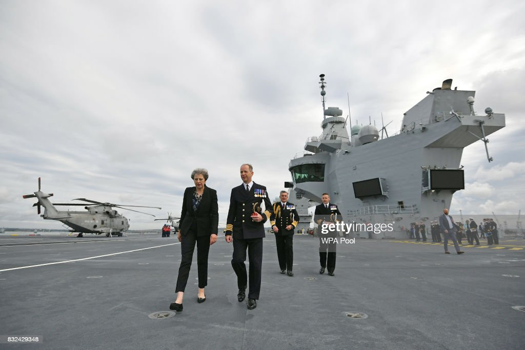 Britain's Prime Minister Theresa May talks with Commodore Jerry Kyd, Captain of the 65,000-tonne British aircraft carrier HMS Queen Elizabeth after it arrived at Portsmouth Naval base, its new home port on August 16, 2017 in Portsmouth, England. The HMS Queen Elizabeth is the lead ship in the new Queen Elizabeth class of supercarriers. Weighing in at 65,000 tonnes she is the largest war ship deployed by the British Royal Navy. She is planned to be in service by 2020 and with a second ship, HMS Prince of Wales, to follow.