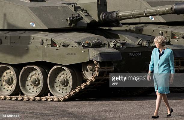 Britain's Prime Minister Theresa May walks npast armoured tanks as she visits the 1st Battalion The Mercian Regiment at their barracks at Bulford...