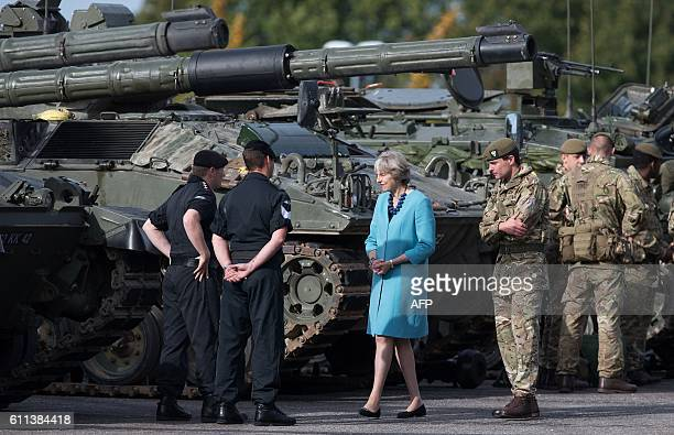 Britain's Prime Minister Theresa May walks past an armoured tank as she talks with troops on her visit to the 1st Battalion The Mercian Regiment at...
