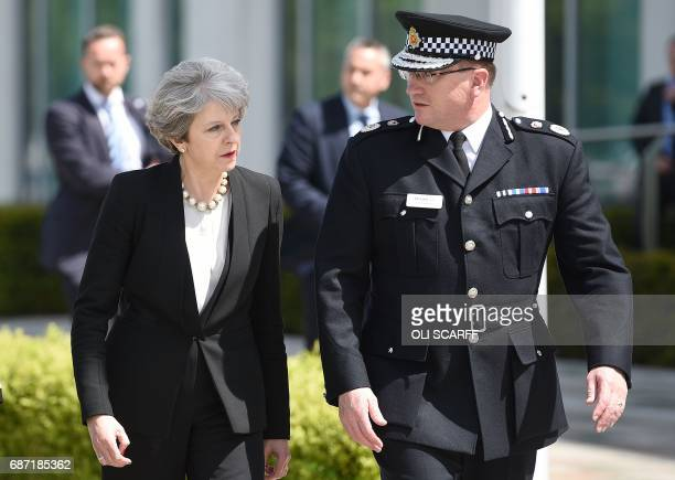 Britain's Prime Minister Theresa May walks with Chief Constable of Greater Manchester Police Ian Hopkins as she arrives at the force's headquarters...