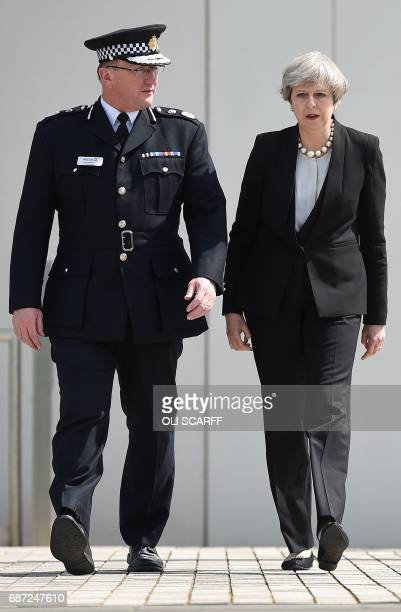 Britain's Prime Minister Theresa May walks with Chief Constable of Greater Manchester Police Ian Hopkins as she leaves following their meeting at the...