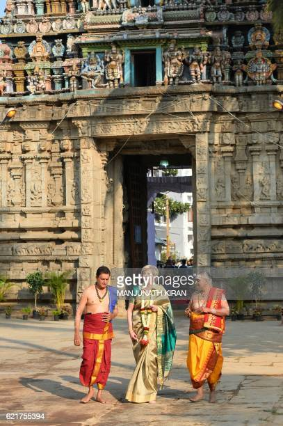 Britain's Prime Minister Theresa May walks with Hindu priests as she arrives to visit the Someshwara Temple in Bangalore on November 8 2016 Britain's...