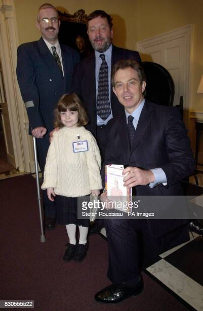Britain's Prime Minister Tony Blair and Education Secretary David Blunkett present Paul and Jessica Wragg from Torbay in Devon with a copy of The...