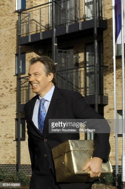 Britain's Prime Minister Tony Blair arrives with a house warming present of a teapot and mugs for Sharon Williams