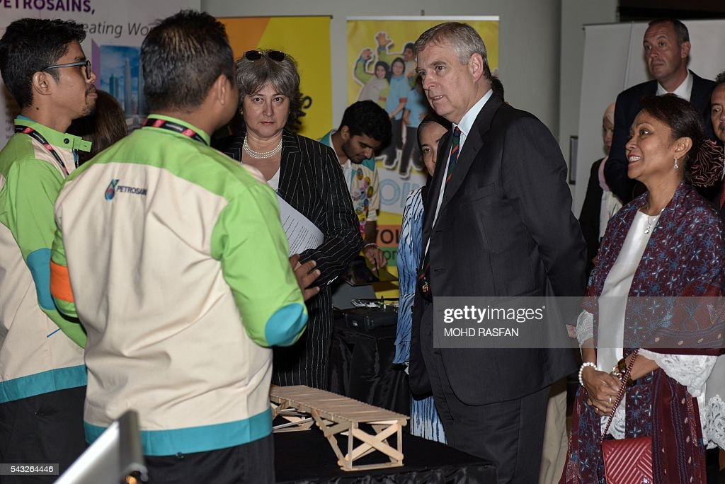 Britain's Prince Andrew (2nd R) listens to a science exhibitor during a visit to the Malaysian science community at Petrosains in Kuala Lumpur on June 27, 2106. Britain's Prince Andrew was at Petrosains Center in Suria KLCC on June 27 for an engagement with the science and research community involved in the Newton-Ungku Omar Fund, a collaborative effort between the British and Malaysian governments to promote science, technology and innovation between the two countries. / AFP / MOHD