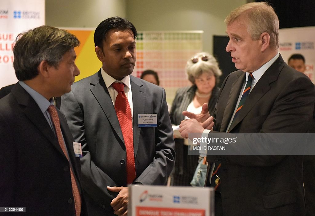 Britain's Prince Andrew (R) talks to science exhibitors during a visit to the Malaysian science community at Petrosains in Kuala Lumpur on June 27, 2106. Britain's Prince Andrew was at Petrosains Center in Suria KLCC on June 27 for an engagement with the science and research community involved in the Newton-Ungku Omar Fund, a collaborative effort between the British and Malaysian governments to promote science, technology and innovation between the two countries. / AFP / MOHD