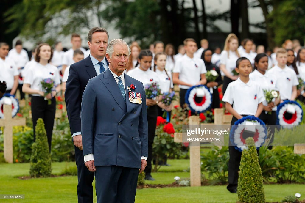 Britain's Prince Charles (front) and British Prime Minister David Cameron (back) stand guard to pay their respect as they attend the memorial ceremony on July 1, 2016, at the Thiepval Memorial in Thiepval, during which Britain and France will mark the 100 years since soldiers emerged from their trenches to begin one of the bloodiest battles of World War I (WWI) at the River Somme. Under grey skies, unlike the clear sunny day that saw the biggest slaughter in British military history a century ago, the commemoration kicked off at the deep Lochnagar crater, created by the blast of mines placed under German positions two minutes before the attack began at 7:30 am on July 1, 1916. / AFP / POOL / Francois Mori