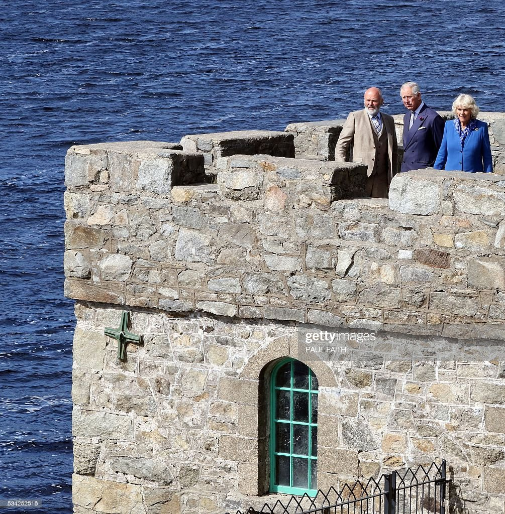 Britain's Prince Charles (C) and his wife Camilla, Duchess of Cornwall (R) are pictured as they speak with Dave Duggan, Divisional Manger, Parks and Wildlife Service, during a tour of the boat house at Glenvagh National Park in Donegal, Ireland, on May 25, 2016. / AFP / PAUL