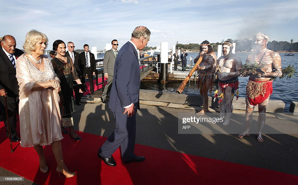 Britain's Prince Charles (C) and his wife Camilla, Duchess of Cornwall (L) walk past an Aboriginal ceremony as they arrive at the Sydney Opera House on November 9, 2012. Britain's Prince Charles and his wife Camilla are in Australia on the second leg of a Diamond Jubilee Tour taking in Papua New Guinea, Australia and New Zealand. AFP PHOTO / POOL / Tim Wimborne