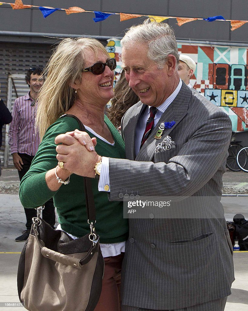 Britain's Prince Charles (R) dances with Lisa Shannon (L) in a 'dance-o-mat' gap filler as he and his wife Camilla (not pictured) visit Oxford Terrace in Christchurch on November 16, 2012. Britain's Prince Charles and his wife Camilla are on the last leg of a tour to mark Queen Elizabeth II's diamond jubilee which has also included Papua New Guinea and Australia and ends on November 16.