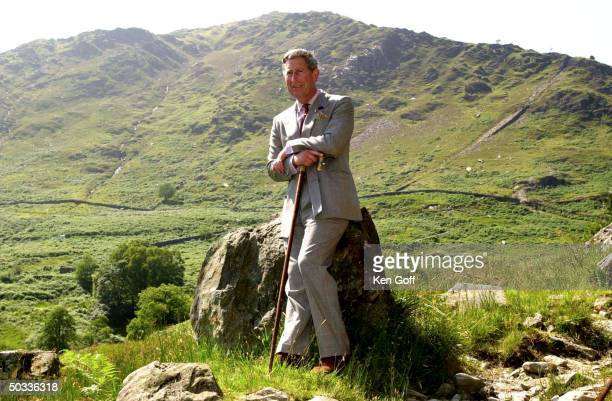 Britain's Prince Charles holding a can while leaning against a rock during a visit to the Hafod y Llan estate