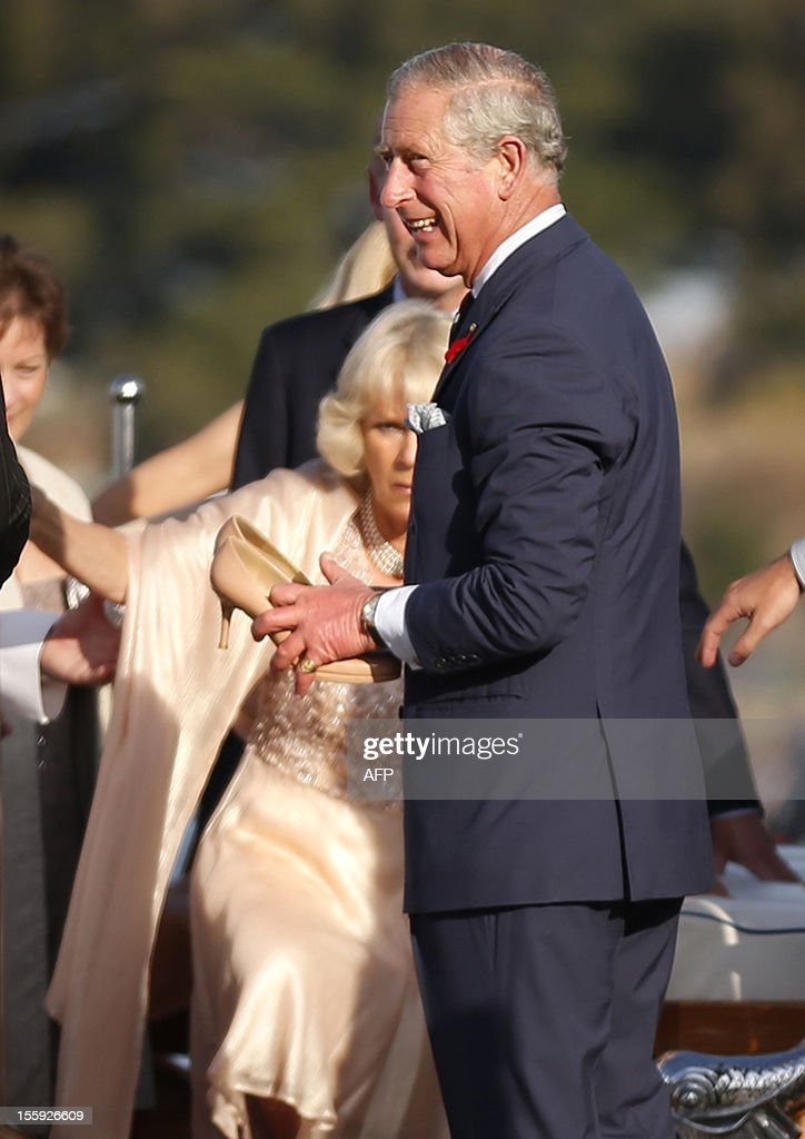 Britain's Prince Charles holds shoes for his wife Camilla, Duchess of Cornwall (background) as she disembarks the Admiral's Barge after crossing Sydney Harbour from Admiralty House to the Sydney Opera House on November 9, 2012. Britain's Prince Charles and his wife Camilla are in Australia on the second leg of a Diamond Jubilee Tour taking in Papua New Guinea, Australia and New Zealand. AFP PHOTO / POOL / Tim Wimborne