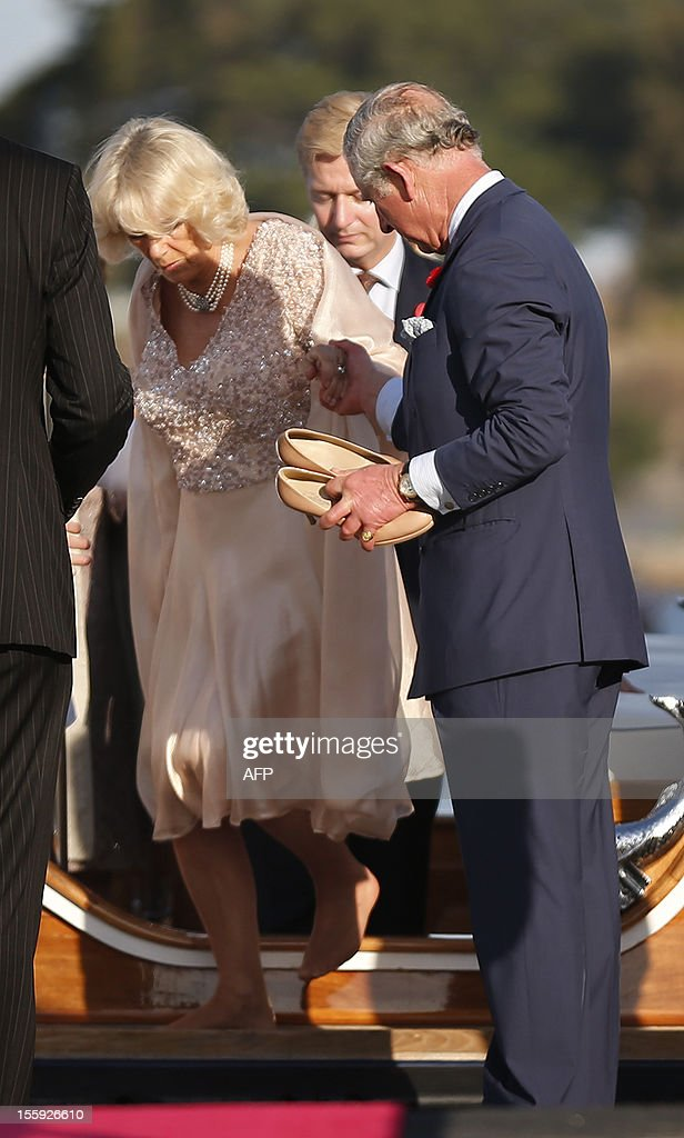 Britain's Prince Charles holds shoes for his wife Camilla, Duchess of Cornwall (L) as she disembarks the Admiral's Barge after crossing Sydney Harbour from Admiralty House to the Sydney Opera House on November 9, 2012. Britain's Prince Charles and his wife Camilla are in Australia on the second leg of a Diamond Jubilee Tour taking in Papua New Guinea, Australia and New Zealand. AFP PHOTO / POOL / Tim Wimborne