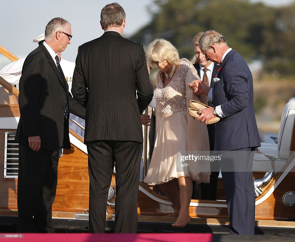 Britain's Prince Charles (R) holds shoes for his wife Camilla, Duchess of Cornwall (C) as she disembarks the Admiral's Barge after crossing Sydney Harbour from Admiralty House to the Sydney Opera House on November 9, 2012. Britain's Prince Charles and his wife Camilla are in Australia on the second leg of a Diamond Jubilee Tour taking in Papua New Guinea, Australia and New Zealand. AFP PHOTO / POOL / Tim Wimborne