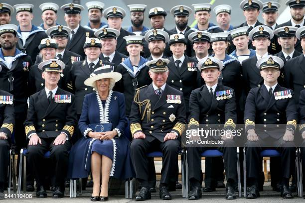TOPSHOT Britain's Prince Charles Prince of Wales and Camilla Duchess of Cornwall pose for an official picture with the ship's company during the...