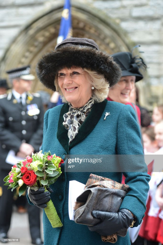 Britain's Prince Charles, Prince of Wales, and Camilla, The Duchess of Cornwall holds a bouquet of flowers she was presented with as she leaves St John The Baptist City Parish Church in Cardiff on March 1, 2013 after attending the St David's Day service. St David is the patron saint of Wales and the annual March 1 feast day is taken as an opportunity to celebrate the nation's culture and heritage.