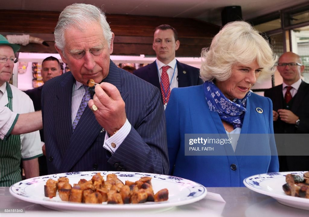 Britain's Prince Charles, Prince of Wales (L) and his wife Britain's Camilla, Duchess of Cornwall prepare to try produce inside McGettigans Butchers store in Donegal, north-west Ireland, on May 25, 2016. / AFP / PAUL