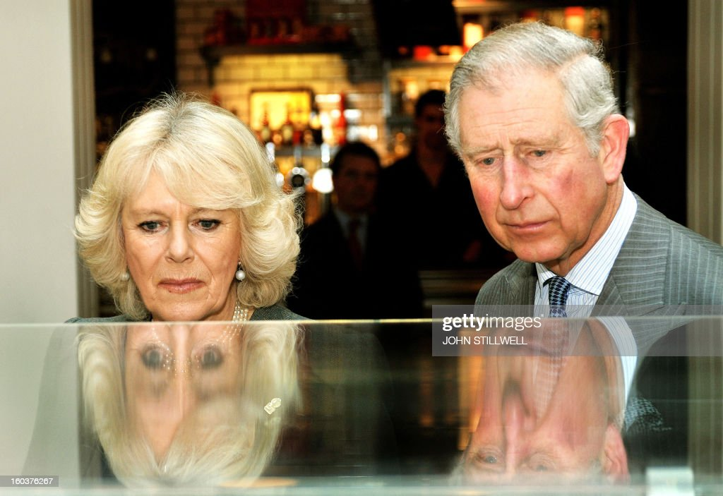 Britain's Prince Charles, Prince of Wales (R), and his wife Camilla, Duchess of Cornwall (L) study a model of the refurbished King's Cross train Station during an event to mark 150 years of the London Underground at Kings Cross in London on January 30, 2013. The London Underground was the world's first underground railway, then known as the Metropolitan Railway, unveiled its first stretch of track between Paddington and Farringdon on January 9, 1863, with passengers making their first journeys a day later. AFP PHOTO / POOL / JOHN STILLWELL
