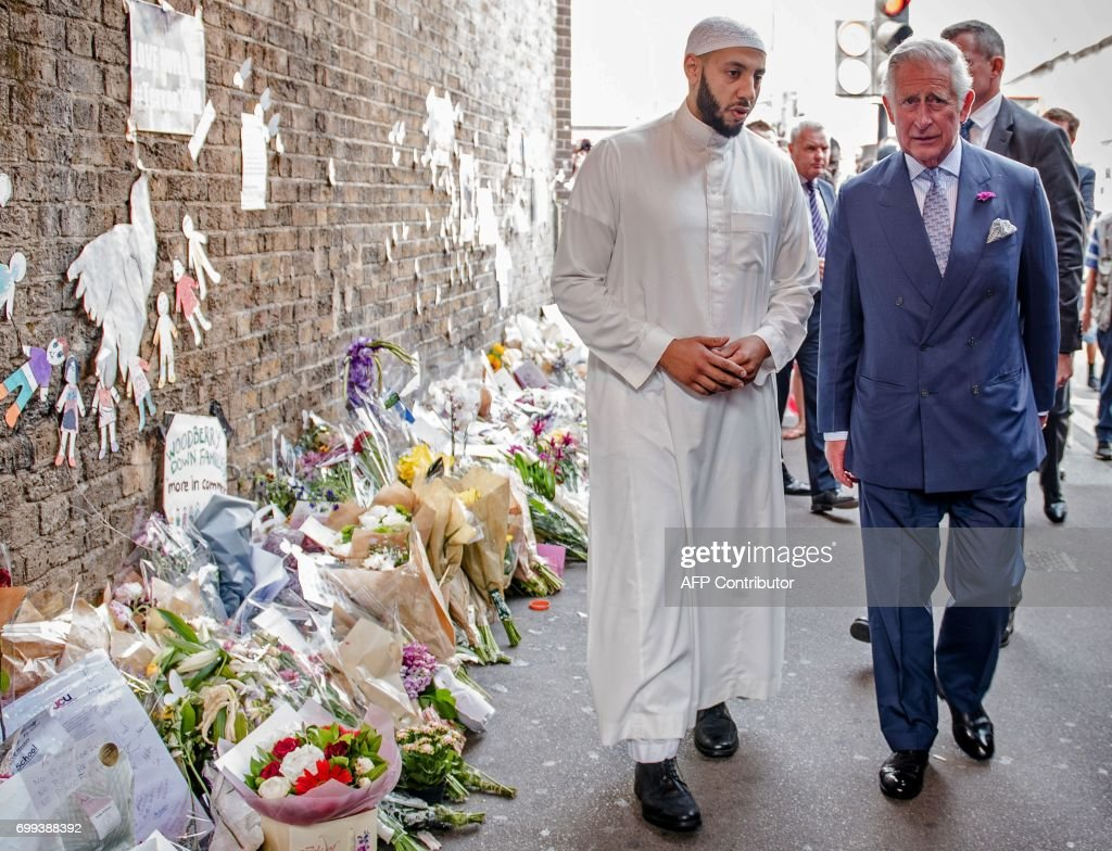 Britain's Prince Charles, Prince of Wales (R) and Imam Mohammed Mahmoud (L) visit floral tributes left close to the scene of the Finsbury Mosque attack in the Finsbury Park area of north London on June 21, 2017, following a vehicle attack on pedestrians. Britain is coming to terms with the aftermath of its fourth bloody assault in three months following Monday's van attack on worshippers leaving the Finsbury Park Mosque in north London. / AFP PHOTO / POOL / John Nguyen