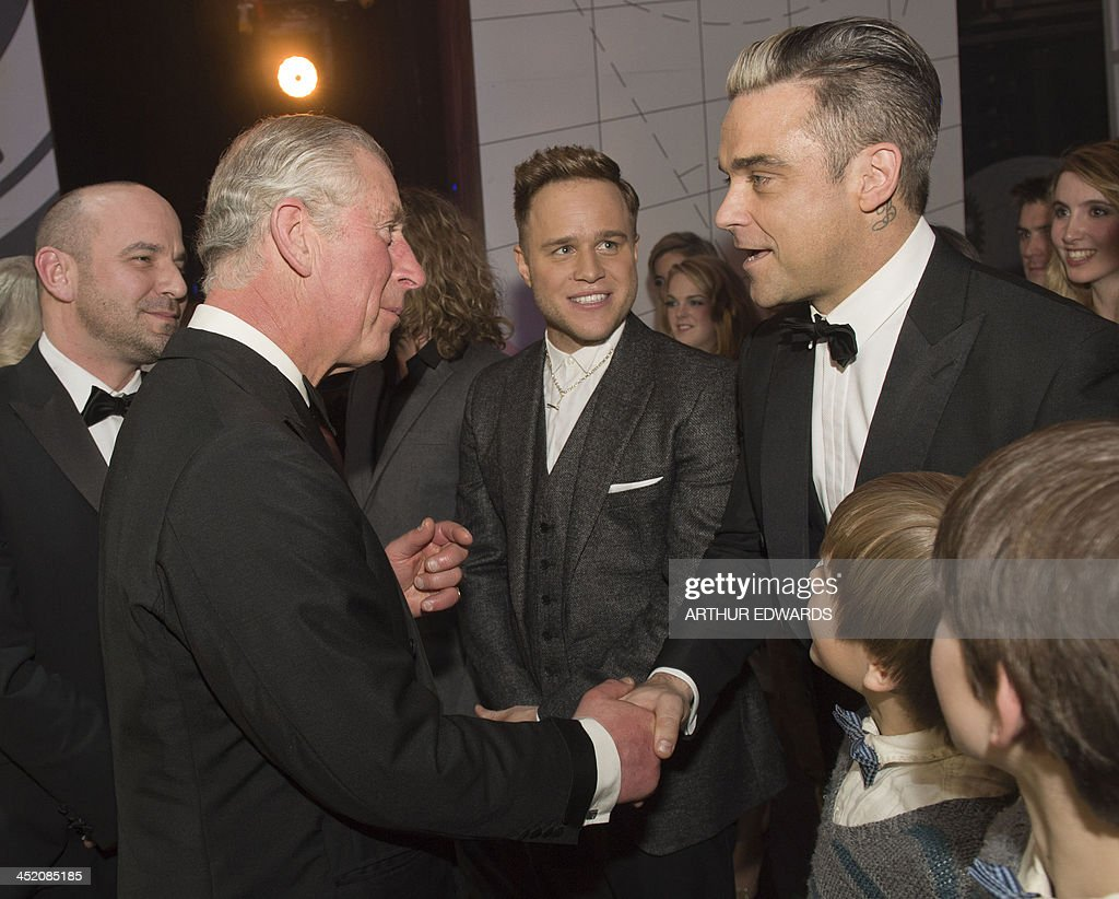 Britain's Prince Charles, Prince of Wales (L) greets British musicians Robbie Williams (R) and Olly Murs (C) as he attends the Royal Variety Performance at the London Palladium Theatre on November 25, 2013. The Royal Variety Performance takes place annually in aid of the Entertainment Artistes Benevolent Fund (EABF) which cares for hundreds of entertainers throughout the UK who need help and assistance as a result of old age, ill-health or hard times. AFP PHOTO / POOL / ARTHUR EDWARDS