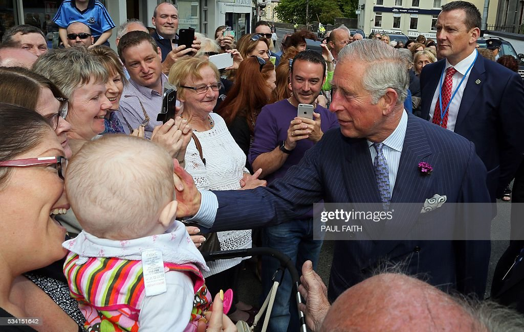 Britain's Prince Charles, Prince of Wales (2R) greets members of the public on a walkbaout through Donegal with his wife, Britain's Camilla, Duchess of Cornwall (unseen) in Donegal, north-west Ireland, on May 25, 2016. / AFP / PAUL