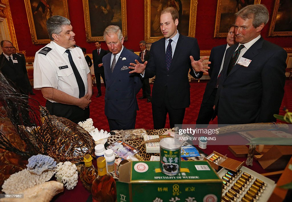Britain's Prince Charles, Prince of Wales (2L), his son Prince William, Duke of Cambridge (3L) and British Environment Secretary Owen Paterson (R) are shown items made from endangered animals, which were confiscated by customs officers, during a conference on the illegal wildlife trade at Clarence House in central London on May 21, 2013. The Royal Highnesses lent their support to efforts to eradicate the trade in items made from highly endangered animals. AFP PHOTO / POOL / ANDREW WINNING