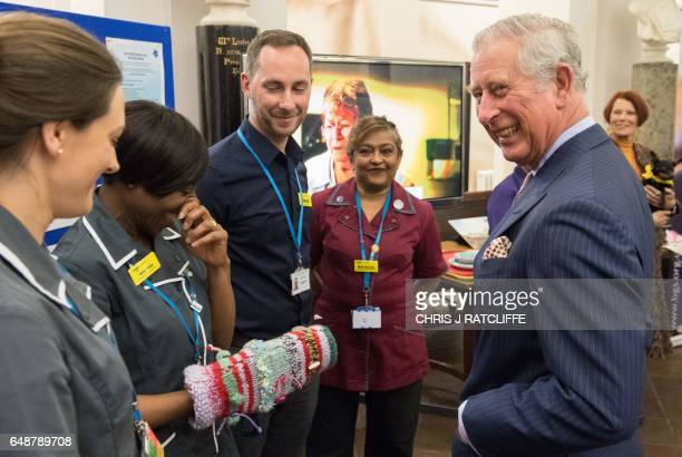 Britain's Prince Charles Prince of Wales reacts as he meets dementia and delirium clinical nurse specialists as one shows him a 'dementia twiddle...
