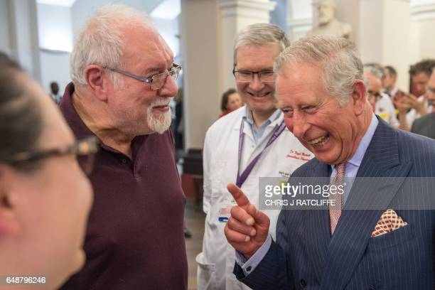 Britain's Prince Charles Prince of Wales reacts as he talks with patient Leon Kreitzman and healthcare professionals during his visit to St Thomas's...