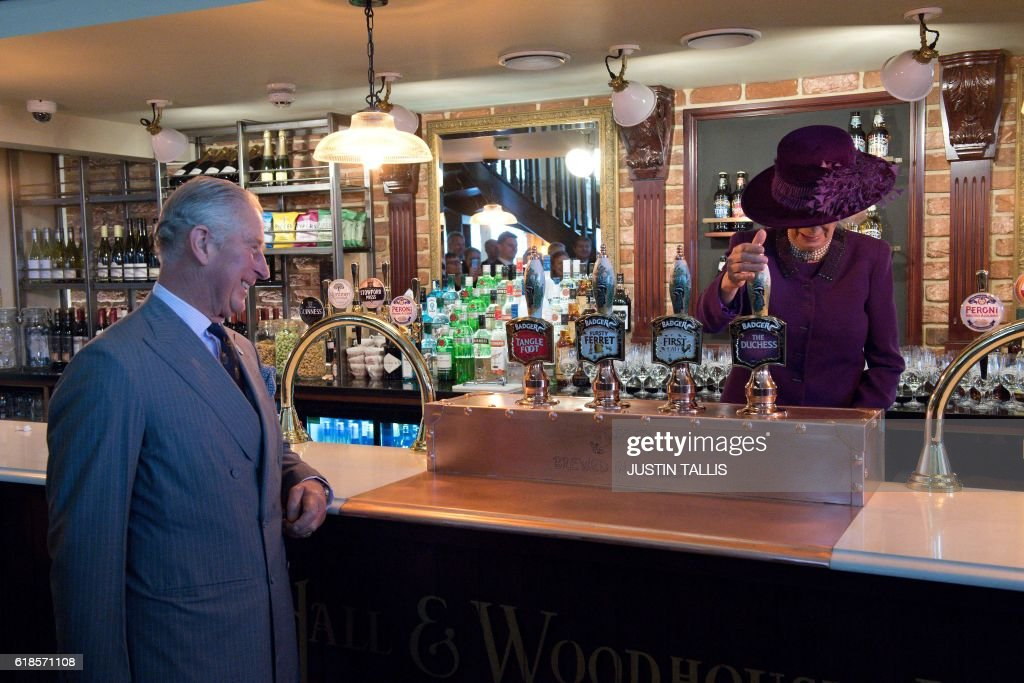 Britain's Prince Charles, Prince of Wales (L) watches as Camilla, Duchess of Cornwall (R) pulls a half pint of 'The Duchess' ale inside the Duchess of Cornwall pub whilst on a visit to the town of Poundbury, southwest England, on October 27, 2016. The Queen and The Duke of Edinburgh, accompanied by The Prince of Wales and The Duchess of Cornwall, visited Poundbury. Poundbury is an experimental new town on the outskirts of Dorchester in southwest England designed by Leon Krier with traditional urban principles championed by The Prince of Wales and built on land owned by the Duchy of Cornwall. / AFP / POOL / JUSTIN