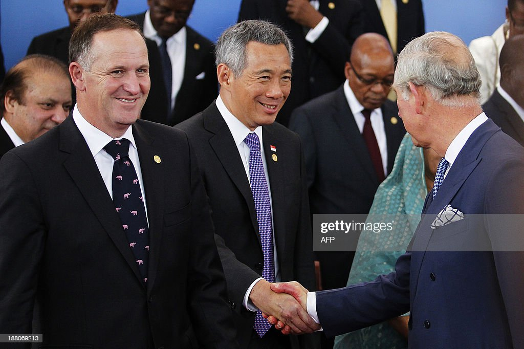 Britain's Prince Charles (R) shakes hands with Prime Minister of Singapore, Lee Hsien Loong (C) as Prime Minister of New Zealand John Key (L) looks on after the official photograph following the opening ceremony of the Commonwealth Heads of Government Meeting (CHOGM) in Colombo on November 15, 2013. Sri Lanka's president urged his peers not to pass judgment over his country's past as he hosted a Commonwealth summit that threatens to be upstaged by a visit to the war-torn north by Britain's David Cameron. AFP PHOTO/POOL/DINUKA LINYANAWATTE