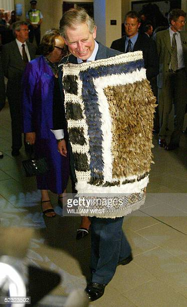 Britain's Prince Charles smiles at weavers after being presented with a traditional Kiwi feather cloak during a visit to an exhibition of traditional...
