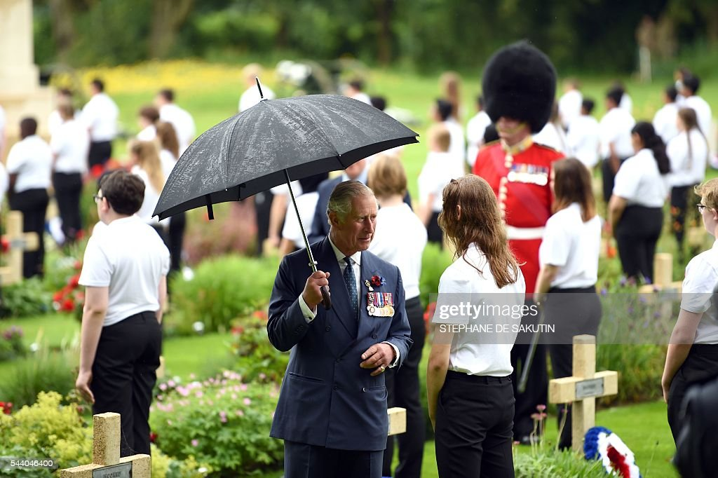 Britain's Prince Charles (C) speaks with a young a woman as he attends the memorial ceremony on July 1, 2016, in Thiepval, during which Britain and France will mark the 100 years since soldiers emerged from their trenches to begin one of the bloodiest battles of World War I (WWI) at the River Somme. Under grey skies, unlike the clear sunny day that saw the biggest slaughter in British military history a century ago, the commemoration kicked off at the deep Lochnagar crater, created by the blast of mines placed under German positions two minutes before the attack began at 7:30 am on July 1, 1916. / AFP / POOL / STEPHANE