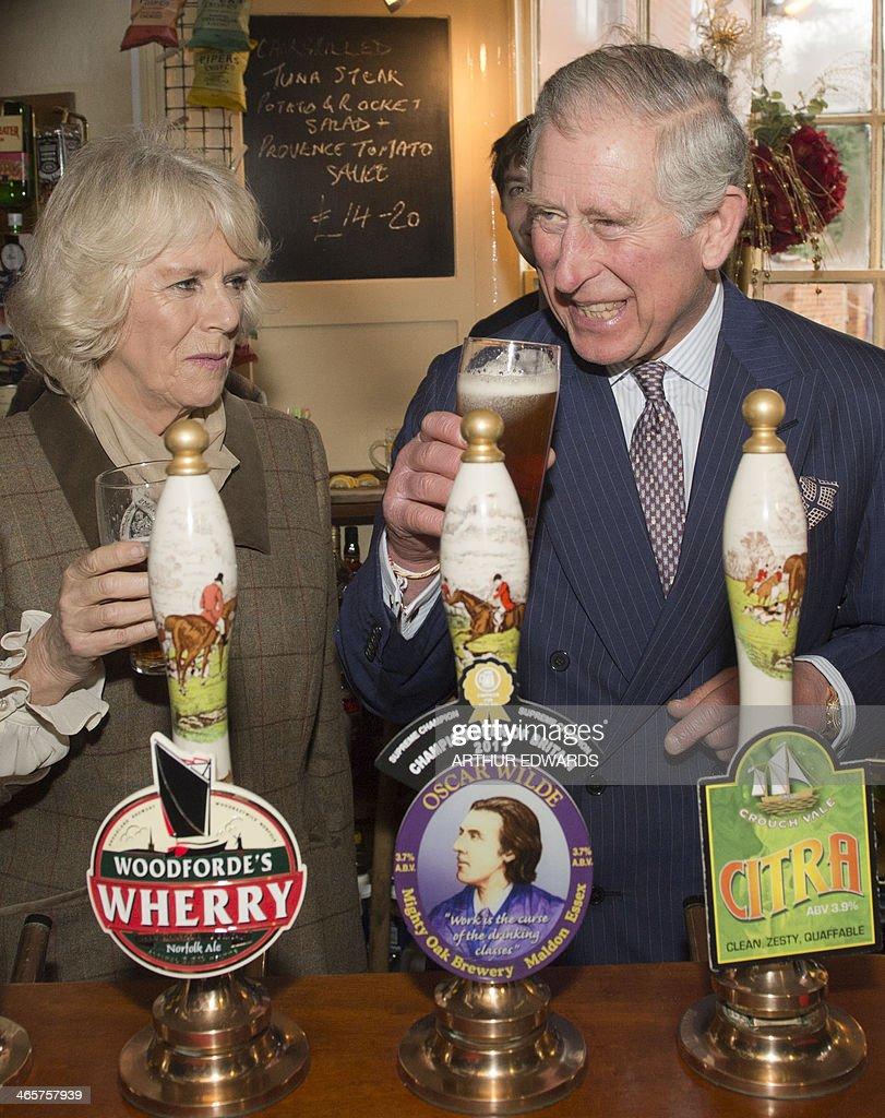 Britain's Prince Charles, The Prince of Wales, (Foreground-R) laughs after pulling a pint of draught beer as Camilla, The Duchess of Cornwall (L) looks on during a visit to The Bell pub in Purleigh on January 29, 2014. AFP PHOTO/POOL/ARTHUR EDWARDS
