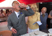 Britain's Prince Charles the Prince of Wales samples an oyster as Camilla the Duchess of Cornwall looks on during a visit to the Whitstable Oyster...