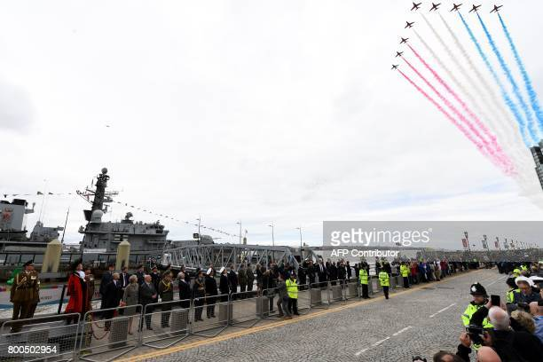 Britain's Prince Edward Earl of Wessex and Britain's Prime Minister Theresa May and spectators watch a flypast by the Red Arrows to mark Armed Forces...