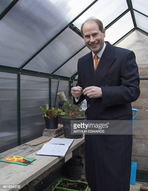 Britain's Prince Edward Earl of Wessex signs a book in a greenhouse during a visit to Tomorrow's People Social Enterprises St Anselm's Church in...