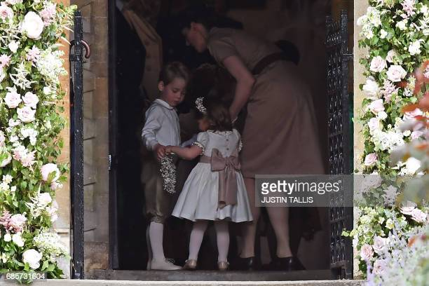 Britain's prince George a pageboy Britain's princess Charlotte a bridesmaid stand with their nanny Maria Borrallo as they attend the wedding of their...