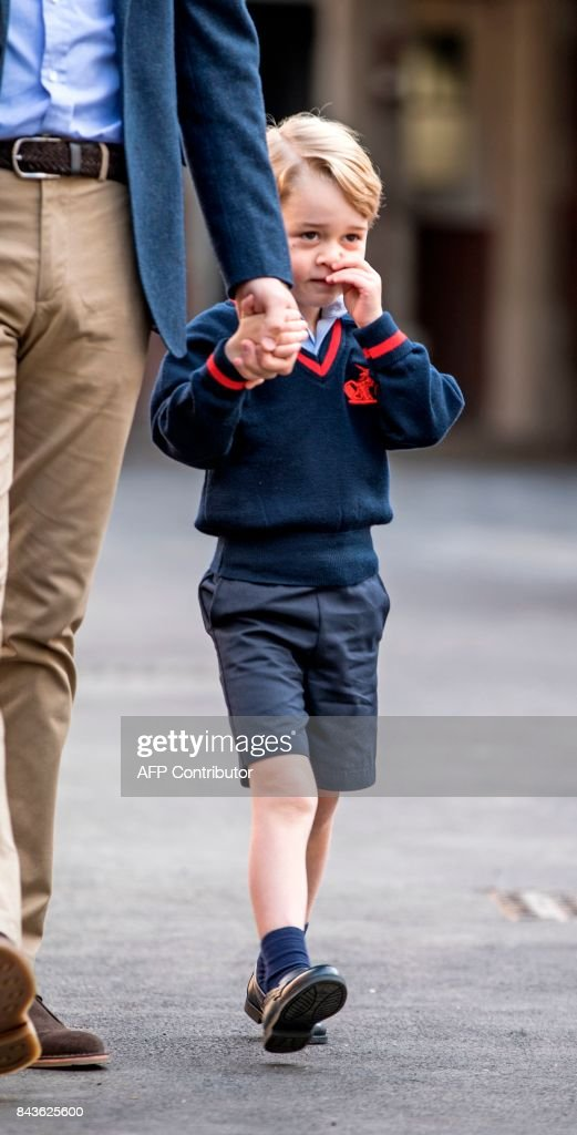 Britain's Prince George accompanied by Britain's Prince William (L), Duke of Cambridge arrives for his first day of school at Thomas's school in Battersea, southwest London on September 7, 2017. /