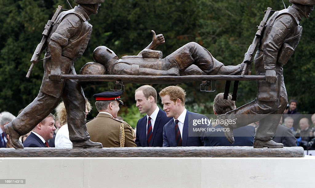 Britain's Prince Harry (R) and his brother Prince William, Duke of Cambridge, walk behind a statue during a visit to Tedworth House, a recovery centre run by the Help for Heroes charity that offers care and support to injured service personnel, in Tidworth, Wiltshire, southern England, on May 20, 2013. The Duke of Cambridge and Prince Harry will officially open four new Help for Heroes recovery centres, which form part of the Defence Recovery Capability.