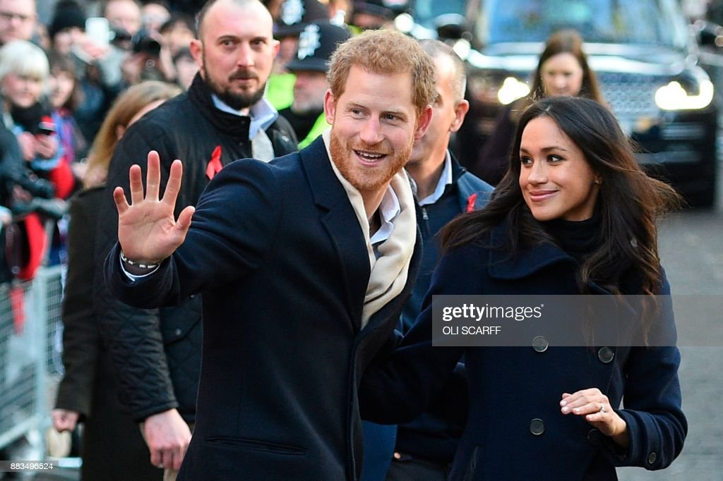 TOPSHOT - Britain's Prince Harry and his fiancee US actress Meghan Markle greet wellwishers on a walkabout as they arrive for an engagement at Nottingham Contemporary in Nottingham, central England, on December 1, 2017 which is hosting a Terrence Higgins Trust World AIDS Day charity fair. Prince Harry and Meghan Markle visited Nottingham in their first set of engagements together since announcing their engagement. / AFP PHOTO / Oli SCARFF