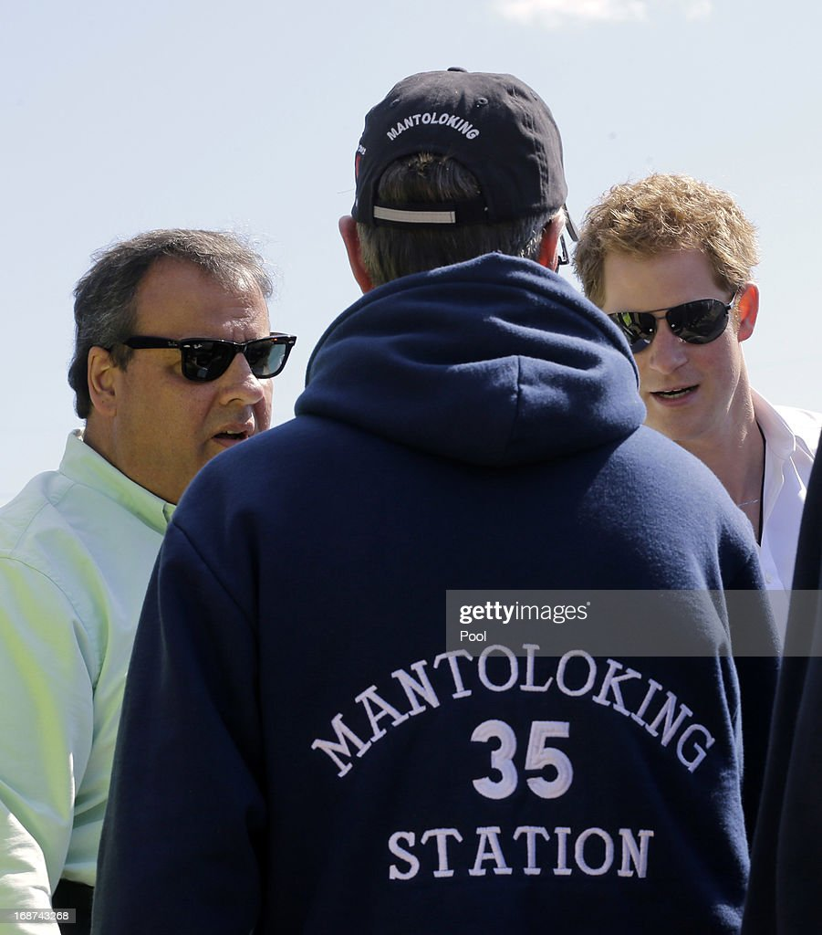 Britain's Prince Harry (R) and New Jersey Gov. Chris Christie (L) greet a Mantoloking firefighter while visiting the area hit by Superstorm Sandy May 14, 2013 in Seaside Heights, New Jersey. New Jersey sustained about $37 billion worth of damage from the storm.