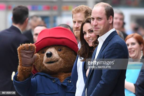 Britain's Prince Harry Britain's Catherine Duchess of Cambridge and Britain's Prince William Duke of Cambridge stand by a person in a Paddington Bear...