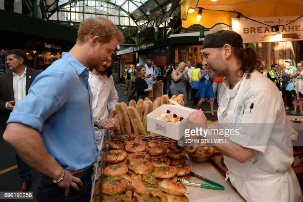 Britain's Prince Harry buys doughnuts as he meets stallholders during a visit to Borough Market in London on June 15 2017 after its reopening...